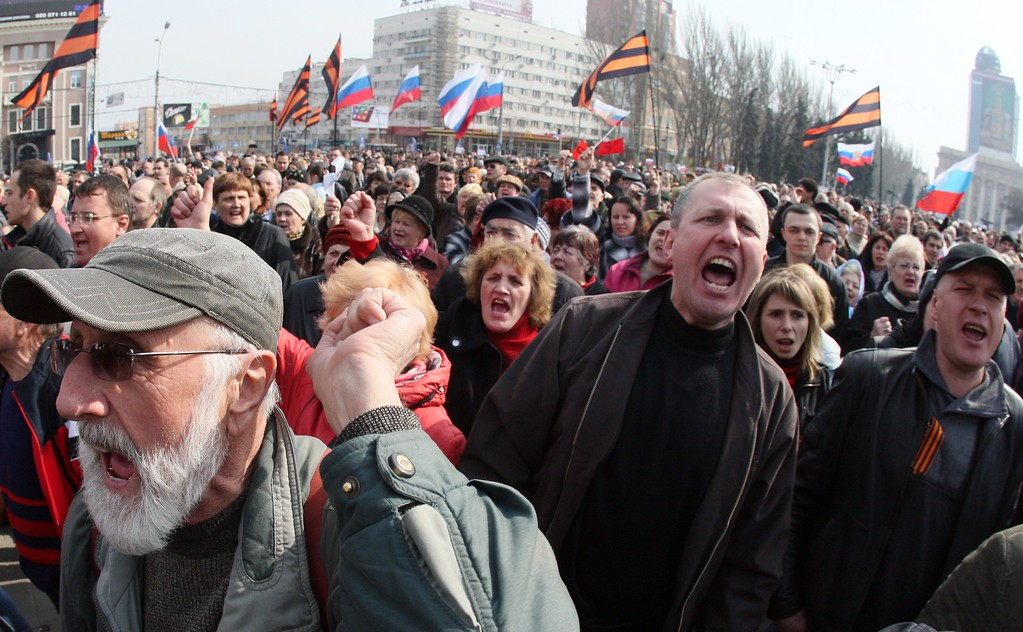 ". Pro-Russian activists shout slogans and hold Russian national flags during a demonstration rally in the center of the eastern Ukrainian city of Donetsk on March 15, 2014. The second successive day of deadly unrest that has now claimed three lives in the mainly Russian-speaking east came hours after Moscow -- its forces already in control of Crimea and conducting snap drills at Ukraine\'s eastern border -- warned that it reserved the right to ""protect\"" compatriots throughout its neighbor. AFP PHOTO / ALEXANDER KHUDOTEPLY/AFP/Getty Images"