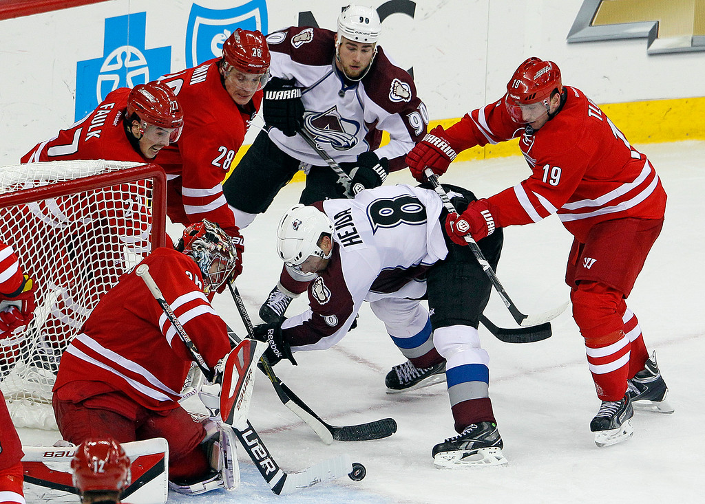 . Colorado Avalanche\'s Jan Hejda (8) and Ryan O\'Reilly (90) battle with Carolina Hurricanes\' Jiri Tlusty (19), of the Czech Republic, Alexander Semin (28), of Russia, Justin Faulk (27) and goalie Justin Peters (35) during the third period of an NHL hockey game in Raleigh, N.C., Tuesday, Nov. 12, 2013. Hurricanes won 2-1. (AP Photo/Karl B DeBlaker)