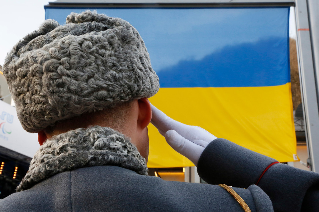 . A Russian honor guard soldier salutes the national Ukrainian flag lifted in honor Vitaly Lukyanenko of Ukraine, winner of the men\'s biathlon men\'s 7.5km, visually impaired event during medal ceremony at the 2014 Winter Paralympic, Sunday, March 9, 2014, in Krasnaya Polyana, Russia. (AP Photo/Dmitry Lovetsky)