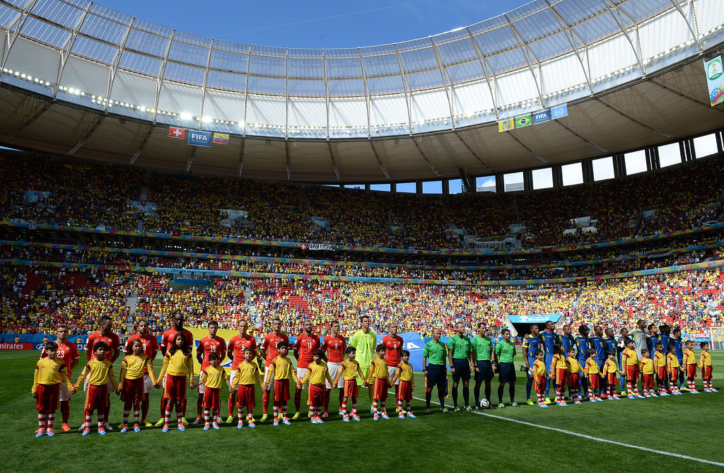 . members of Swiss national team (L) and Ecuadorian team listen to national anthems prior to a Group E football match between Switzerland and Ecuador at the Mane Garrincha National Stadium in Brasilia during the 2014 FIFA World Cup on June 15, 2014.    AFP PHOTO/ ANNE-CHRISTINE POUJOULAT
