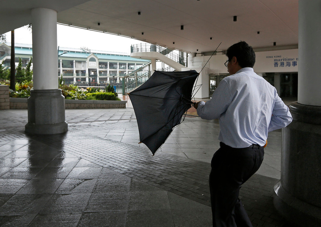 . A man battles against strong wind at a ferry pier in Hong Kong Tuesday, Aug. 13, 2013. The Observatory said Typhoon Utor intensified slightly as it moves towards the western coast of Guangdong. The typhoon battered the northern Philippines on Monday, toppling power lines and dumping heavy rain across cities and food-growing plains. (AP Photo/Vincent Yu)