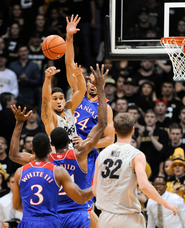 . Colorado University point guard, Askia Booker, top left, looks for an open teammate against the defense of Kansas forward, Landen Lucas, top right, in the first half of play at the Coors Events Center in Boulder Colorado Saturday afternoon, December 07, 2013. (Photo By Andy Cross/The Denver Post)