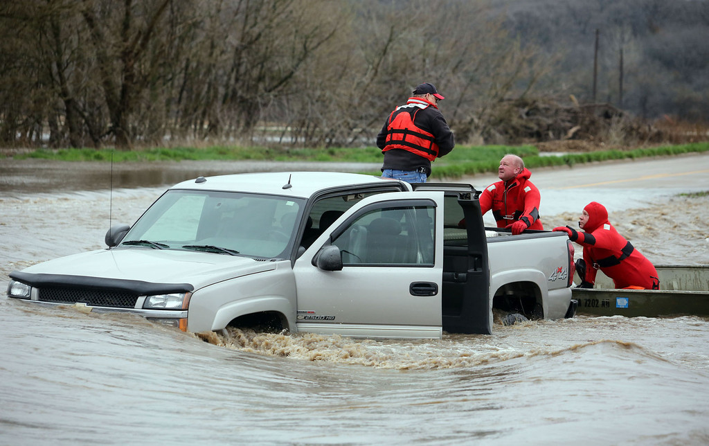 . Members of the Burlington, Iowa, Fire Department Ky Duttlinger, center, and Greg Higdon, right, rescue Mike Schnedler, Burlington, from the back of his  pickup truck, Thursday April 18, 2013, after it was swept off of Flint Bottom Road in Burlington, Iowa.   Schnedler attempted to drive through the standing water covering the road. (AP Photo/The Hawk Eye, John Lovretta)