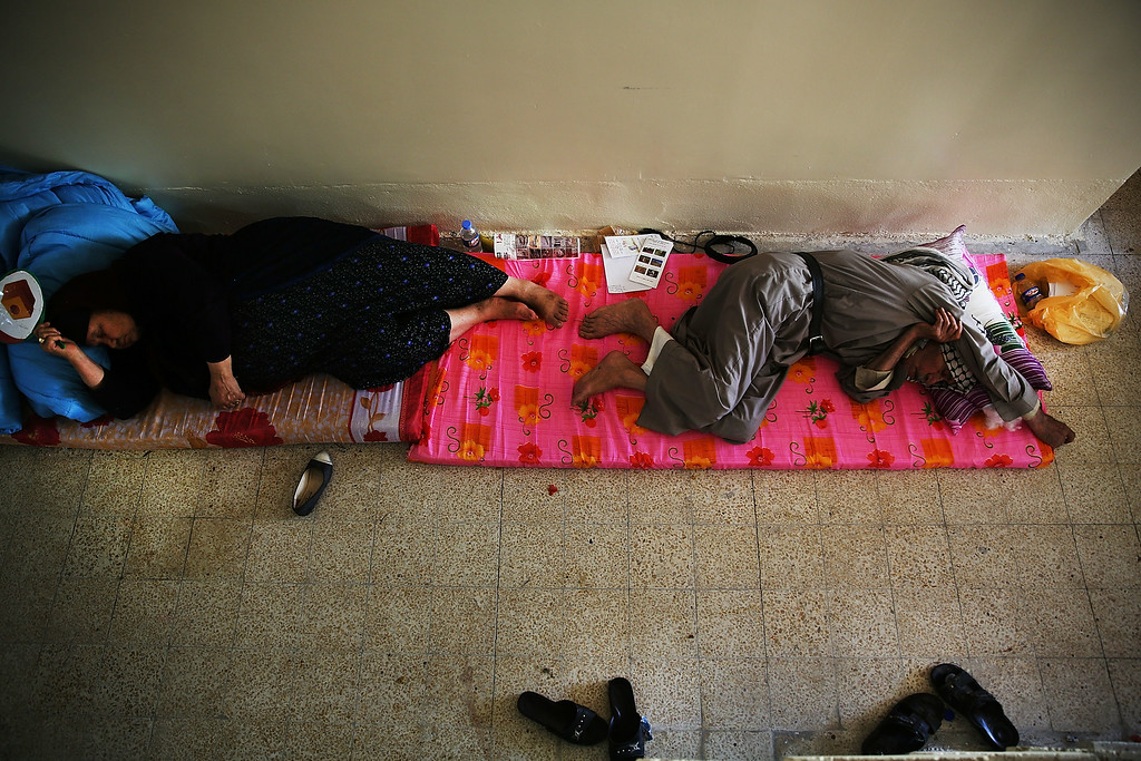 . ARBIL, IRAQ - JUNE 27: An elderly Iraqi Christian couple sleep on the floor at Saint Joseph\'s church where they are living with hundreds of other Christians after having to flee their district on June 26, 2014 in Erbil, Iraq. Tens of thousands of people have fled Iraq\'s second largest city of Mosul after it was overrun by ISIS (Islamic State of Iraq and Syria) militants. Many have been temporarily housed at various IDP camps around the region including the area close to Erbil, as they hope to enter the safety of the nearby Kurdish region. Christians, Shiites and Kurdish Iraqis have received the brunt of the violence from the militants.  (Photo by Spencer Platt/Getty Images)