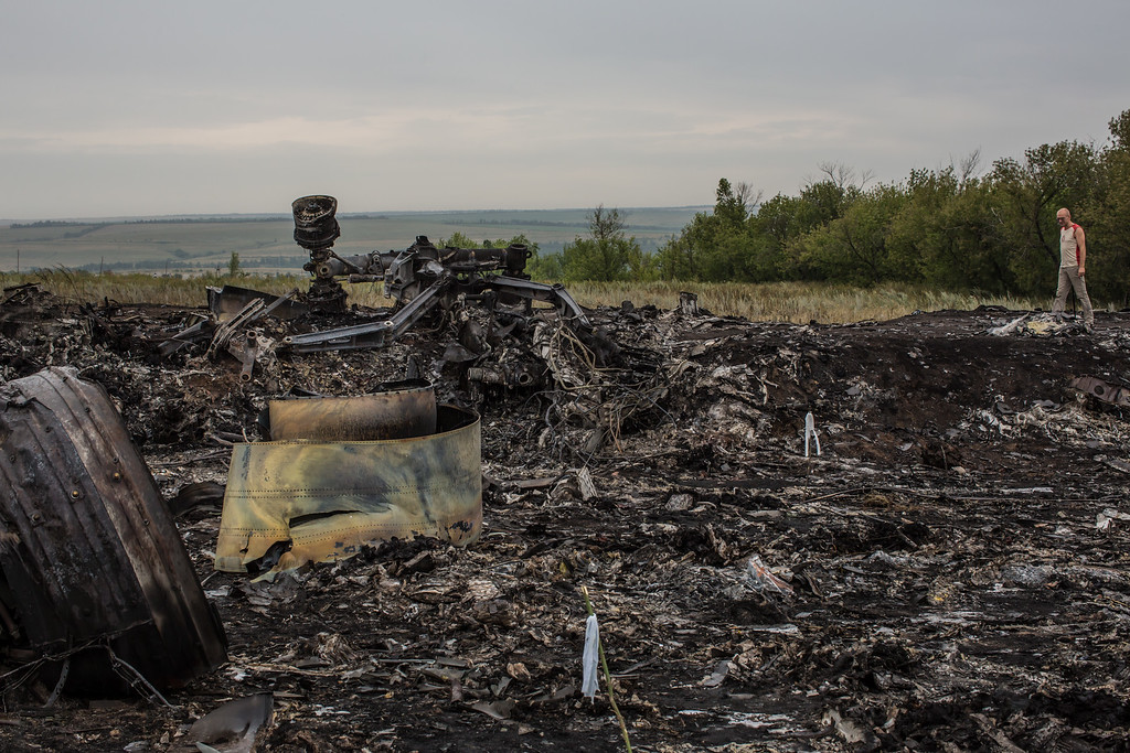 . A man looks at debris from an Air Malaysia plane crash on July 18, 2014 in Grabovka, Ukraine. Air Malaysia flight MH17 travelling from Amsterdam to Kuala Lumpur crashed yesterday on the Ukraine/Russia border near the town of Shaktersk. The Boeing 777 was carrying 298 people including crew members, the majority of the passengers being Dutch nationals, believed to be at least 173, 44 Malaysians, 27 Australians, 12 Indonesians and 9 Britons.    (Photo by Brendan Hoffman/Getty Images)