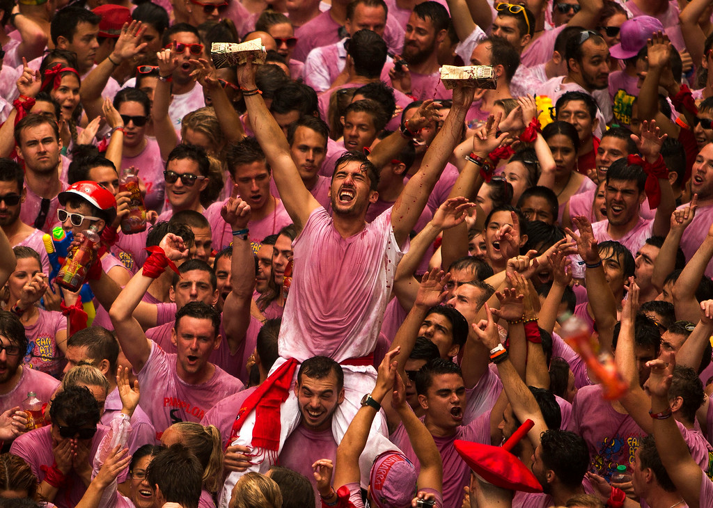 ". Revelers throw wine before the launch of the ""Chupinazo\"" rocket, to celebrate the official opening of the 2014 San Fermin fiestas in Pamplona, Spain, Sunday, July 6, 2014. Revelers from around the world turned out to kick off the festival with a messy party in the Pamplona town square, one day before the first of eight days of the running of the bulls glorified by Ernest Hemingway\'s 1926 novel \""The Sun Also Rises.\"" (AP Photo/Andres Kudacki)"