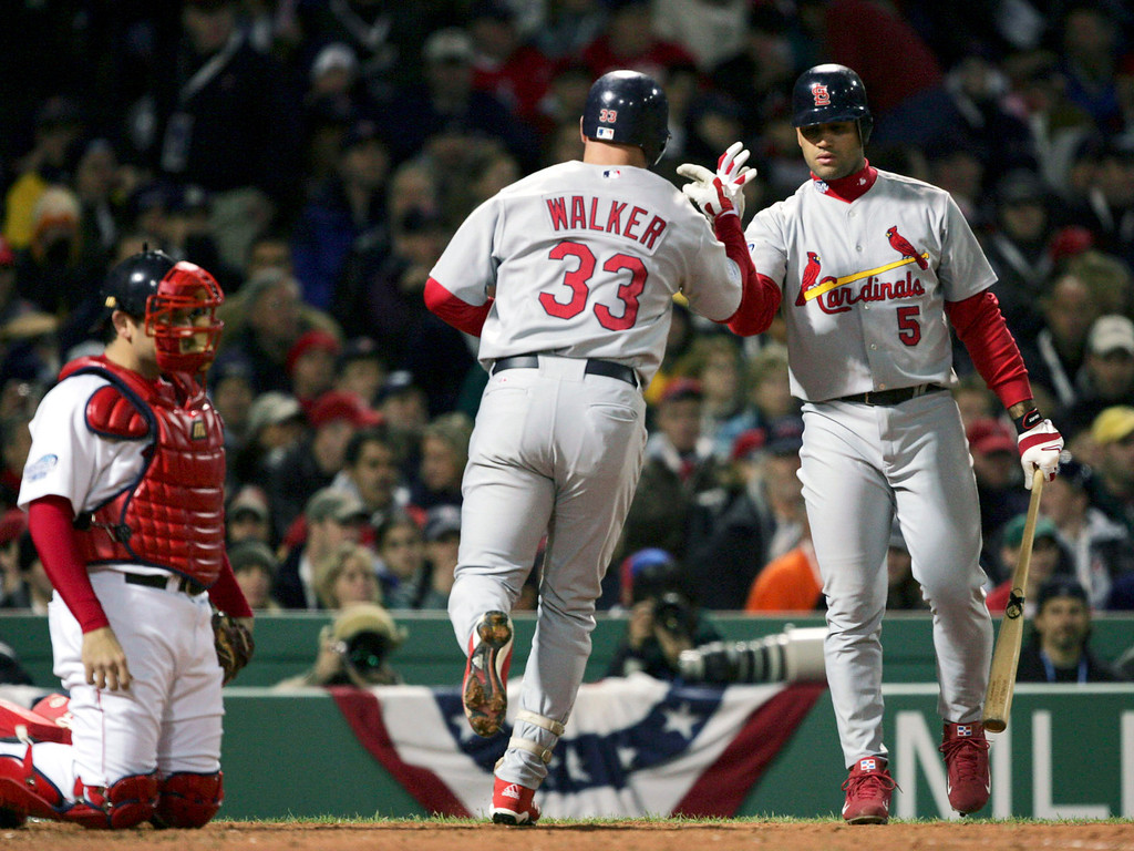 . St. Louis Cardinal\'s Albert Pujols (5) congratulates teammate Larry Walker (33) after hitting a home run in the third inning of Game 1 of the World Series Saturday, Oct. 23, 2004, in Boston, as Boston Red Sox catcher Doug Mirabelli looks on.  (AP Photo/Charles Krupa)
