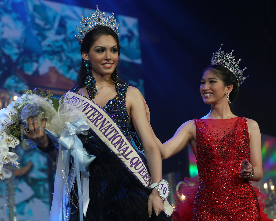 . Marceki Ohio of Brazil, left, is congratulated by Miss International Queen 2012 Kevin Balot of the Philippines, right, after winning the Miss International Queen 2013 transgender beauty pageant in Pattaya, southeastern Thailand Friday, Nov. 1, 2013. (AP Photo/Apichart Weerawong)