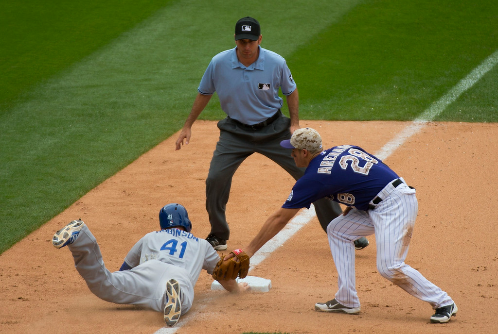 . Los Angeles Dodgers first baseman Clint Robinson (41) dives back to third just under the tag of Colorado Rockies third baseman Nolan Arenado (28) during the eight inning July 6, 2014 at Coors Field. (Photo by John Leyba/The Denver Post)