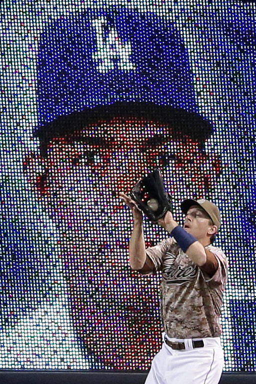 . San Diego Padres right fielder Chris Denorfia makes the catch for the out on Los Angeles Dodgers\' Yasiel Puig, in front of an outfield wall screen image of Puig during the eighth inning of an opening night baseball game on Sunday, March 30, 2014, in San Diego. (AP Photo/Gregory Bull)