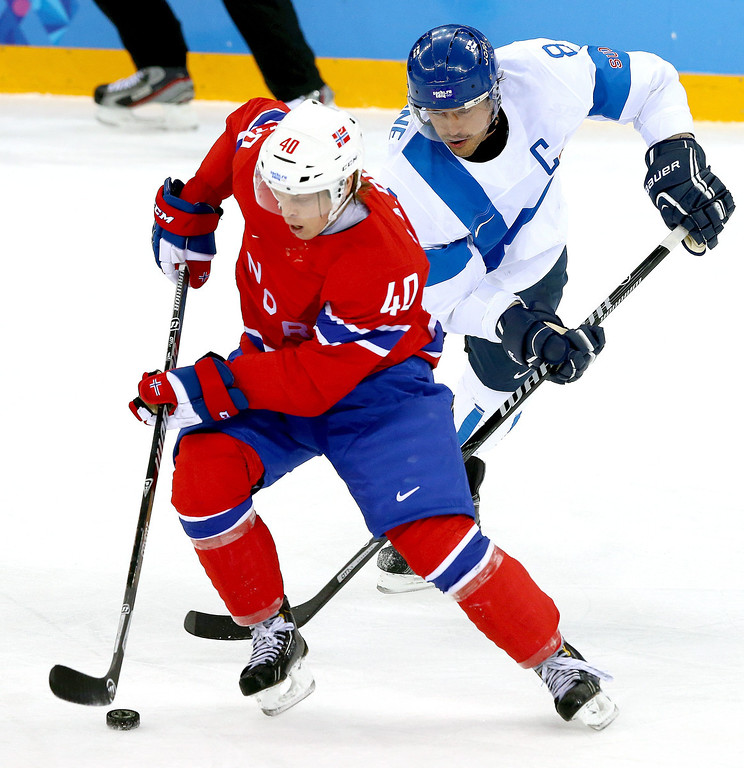 . Ken Andre Olimb (L) of Norway in action against Teemu Selanne (R) of Finland during the Men\'s Preliminary Round Group B match between Norway and Finland at the Shayba Arena in the Ice Hockey tournament at the Sochi 2014 Olympic Games, Sochi, Russia, 14 February 2014.  EPA/SRDJAN SUKI