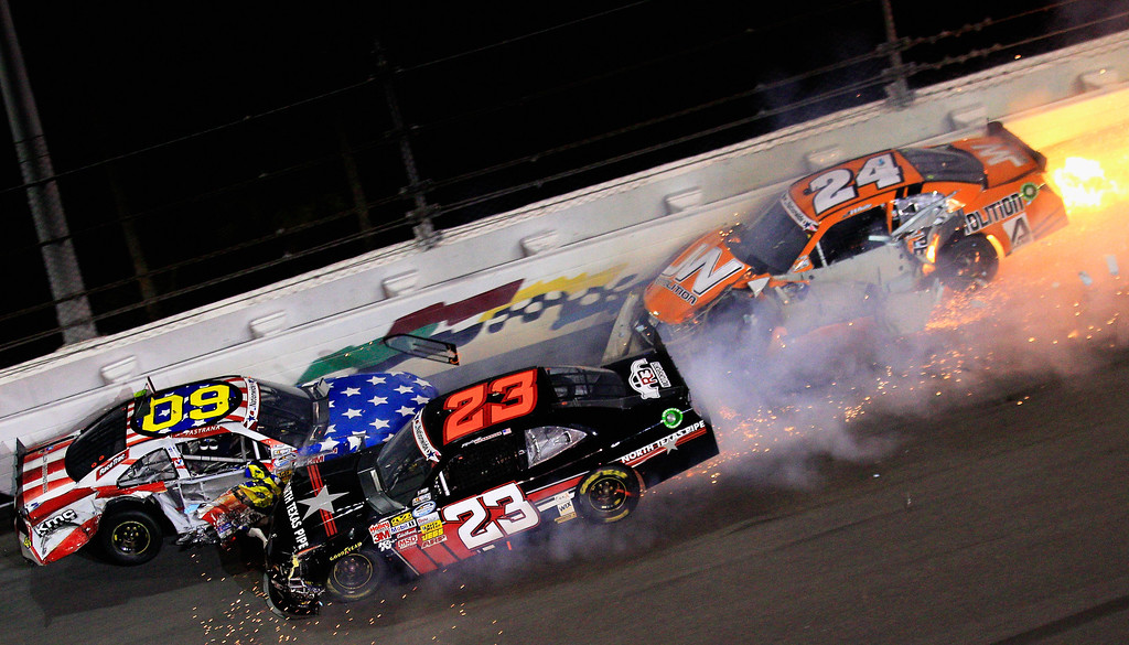 . DAYTONA BEACH, FL - JULY 05:  (L-R) Travis Pastrana, driver of the #60 Roush Fenway Racing / RaceTrac FoTrevor Bayne, driver of the #6 Cargill / Winn-Dixie Ford, Robert Richardson Jr., driver of the #23 North Texas Pipe Chevrolet and Jason White , driver of the #24 JW Demolition Toyota are involved in a wreck along the wall during the NASCAR Nationwide Series Subway Firecracker 250 at Daytona International Speedway on July 5, 2013 in Daytona Beach, Florida.  (Photo by Sean Gardner/Getty Images)