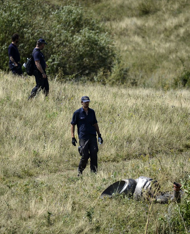 . Dutch experts examine the area of the Malaysia Airlines Flight 17 plane crash in the village of Hrabove (Grabovo), some 80km east of Donetsk, on August 2, 2014. Shelling on August 2, 2014 forced international experts to abandon part of the crash scene of the downed Malaysia Airlines jet in east Ukraine as sniffer dogs working elsewhere on the vast site helped uncover the remains of more victims. 298 people were killed when the Malaysian airliner was shot down over Ukraine on July 17. BULENT KILIC/AFP/Getty Images