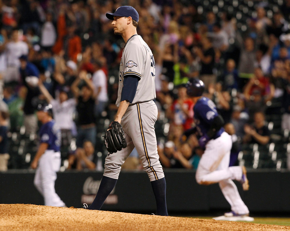 . Milwaukee Brewers relief pitcher John Axford, front, reacts as Colorado Rockies\' Troy Tulowitzki, back, circles the bases after hitting a solo home run off Axford to lead off the bottom of the eighth inning of a baseball game in Denver on Saturday, July 27, 2013. (AP Photo/David Zalubowski)