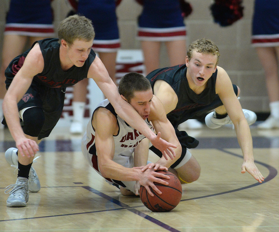 . LITTLETON, CO. - JANUARY 17: Dakota Ridge guard Jacob Flores (4) scrambled for a loose ball and got sandwiched by Chatfield\'s Andrew St. Germain, left, and Darius Reiter, right, in the second half. The Dakota Ridge High School boy\'s basketball team hung on to beat Chatfield 53-51 Friday night, January 17, 2014. Photo By Karl Gehring/The Denver Post