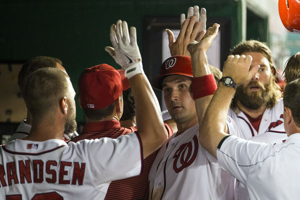 . Washington Nationals Ryan Zimmerman is congratulated by teammates after scoring on a three-run double by Ian Desmond during the sixth inning of a baseball game against the Colorado Rockies at Nationals Park, on Monday, June 30, 2014, in Washington. (AP Photo/ Evan Vucci)