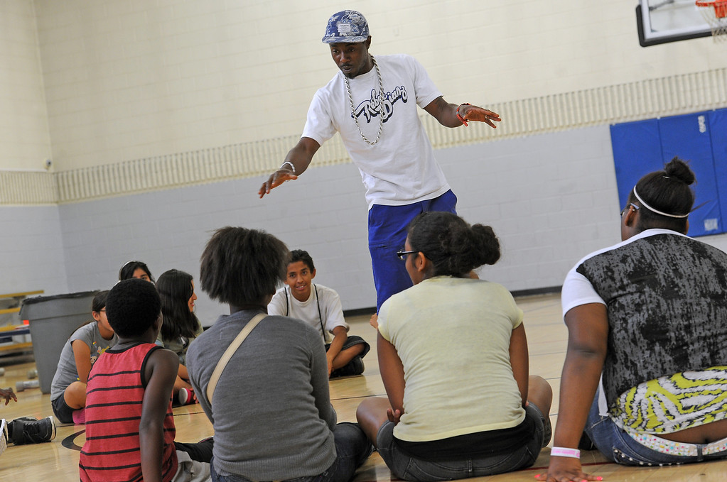 """. DENVER, CO - JULY 1:  DJ Caven Moetavation talks to kids during a summer camp at St. Charles Recreation Center at 3777 Lafayette Street in Denver, CO. on July 1, 2013.  DJ Cavem Moetavation aka Ietef Vita, and his wife Neambe Leadon Vita, not shown, hold the camp to introduce kids to healthy eating habits, teach them about organic farming and changing the way they think about food. They also make organic juice during the day using produce from the couple\'s garden which includes cucumbers, strawberries, watermelon, kale, lime and coconut water.   As part of our \""""Summer of Love\"""" series for the Style section we profile the relationship of DJ Cavem Moetavation (a.k.a. Ietef Vita) and his wife Neambe Vita.  They are proud and longtime Five Points residents. They\'re artists, community activists, musicians, teachers and more.  They espouse the idea of being vegan or vegetarian and promote eating healthfully and organically.  (Photo by Helen H. Richardson/The Denver Post)"""