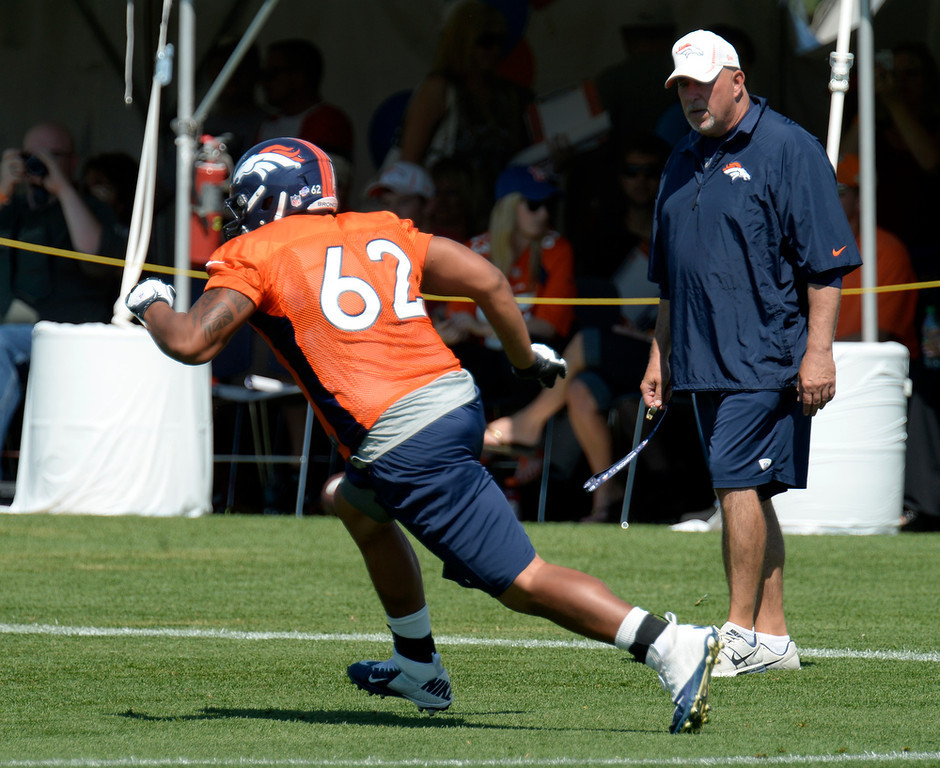 . Denver Broncos offensive line coach Dave Magazu watches Manase Foketi (62) hit the blocking dummy during practice August 19, 2013 at Dove Valley (Photo by John Leyba/The Denver Post)
