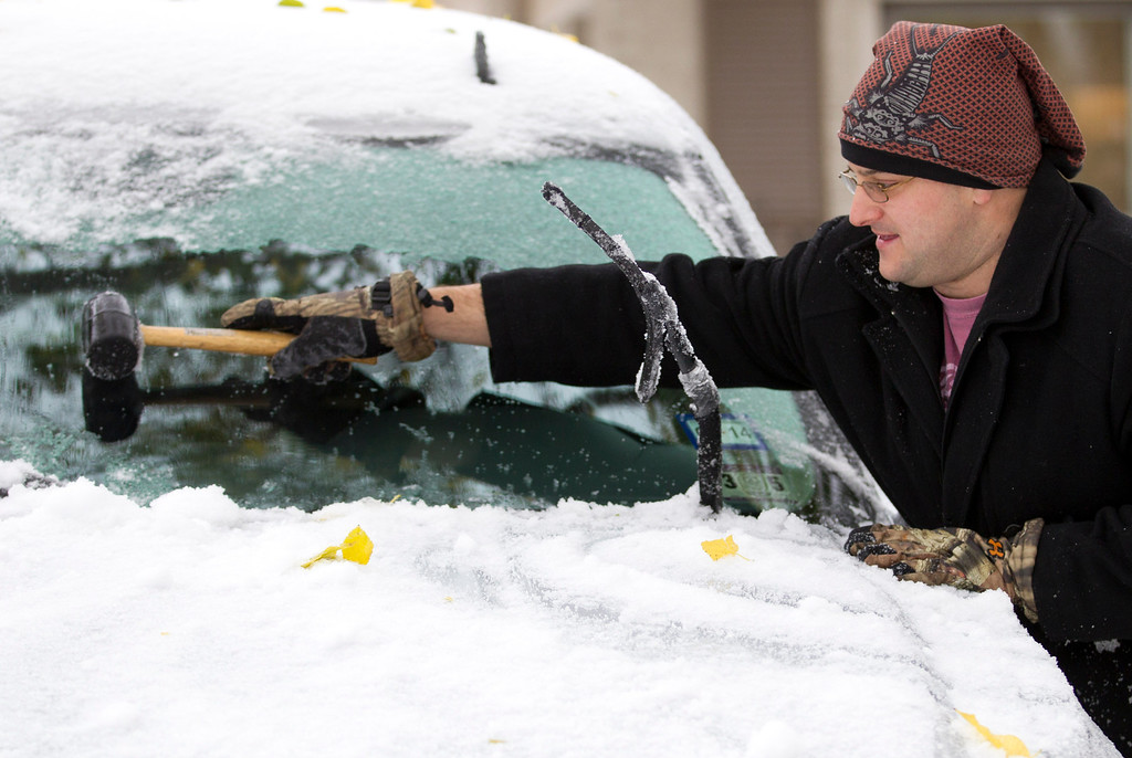 . Hunter Semple uses a rubber mallet to clear the ice from the windshield of his new vehicle in Fort Worth, Texas on Friday, Dec. 6, 2013. Winter storm and ice warnings are in effect through much of today for parts of six states in the Midwest, including Texas, Missouri, Illinois and Indiana. (AP Photo/The Fort Worth Star-Telegram, Joyce Marshall)