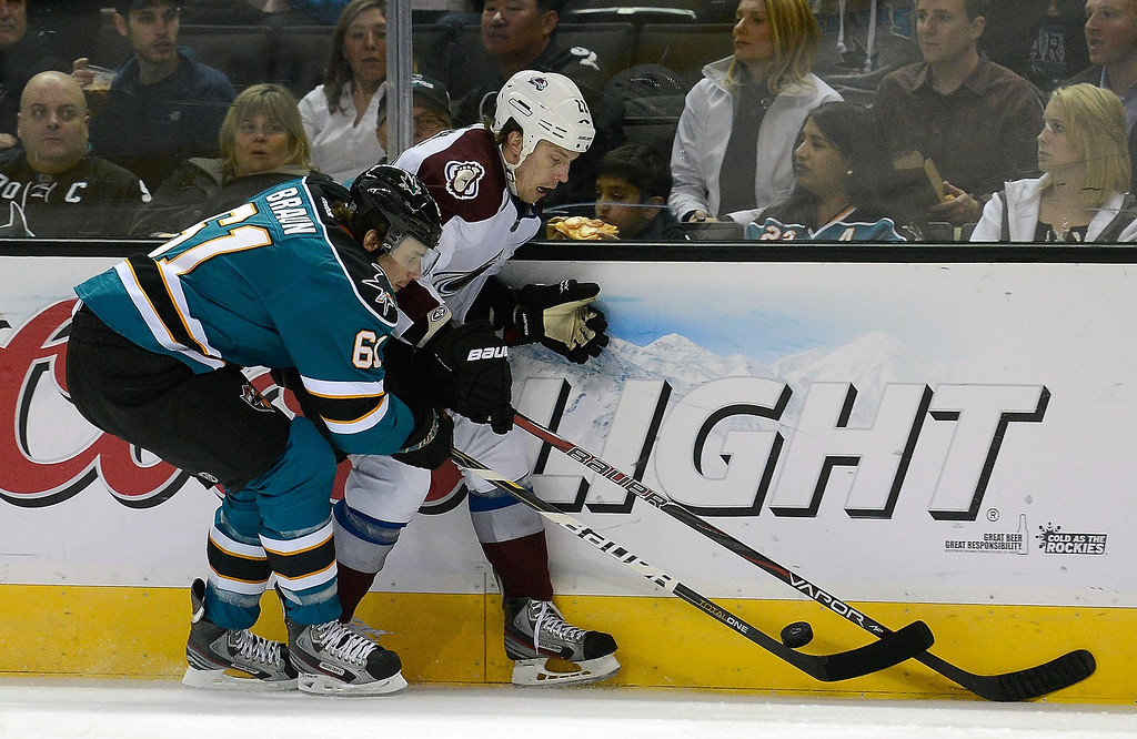 . Matt Hunwick #22 of the Colorado Avalanche battles for control of the puck with Justin Braun #61 of the San Jose Sharks in the first period at HP Pavilion on February 26, 2013 in San Jose, California.  (Photo by Thearon W. Henderson/Getty Images)
