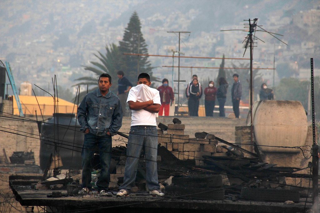 . Residents stand on a charred rooftop in the Mexico City suburb of Ecatepec, where a gas tanker truck exploded on the highway, early Tuesday, May 7, 2013. The blast killed and injured dozens, according to the Citizen Safety Department of Mexico State. Officials did not rule out the possibility the death toll could rise as emergency workers continued sifting through the charred remains of vehicles and homes built near the highway on the northern edge of the metropolis. (AP Photo/Gabriela Sanchez)