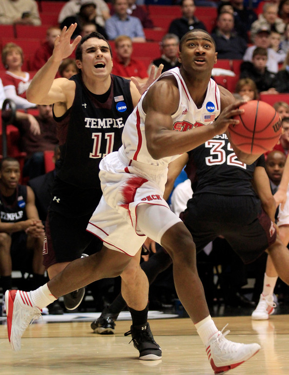 . CORRECTS BYLINE - North Carolina State guard Rodney Purvis drives past Temple guard T.J. DiLeo (11) in the first half of a second-round game at the NCAA college basketball tournament, Friday, March 22, 2013, in Dayton, Ohio. (AP Photo/Skip Peterson)