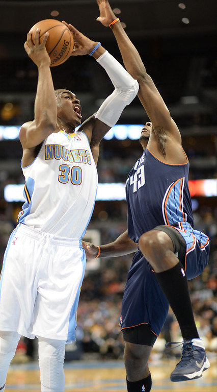 . Quincy Miller of the Denver Nuggets (30), left, drives and score the basket against Anthony Tolliver of Charlotte Bobcats (43) in the first half. (Photo by Hyoung Chang/The Denver Post)