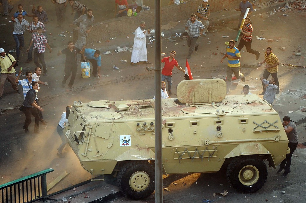 . Supporters of ousted Islamist President Mohammed Morsi capture an Egyptian security forces vehicle at the Ministry of Finance in Cairo, Egypt, Wednesday, Aug. 14, 2013.  (AP Photo/Mohsen Nabil)