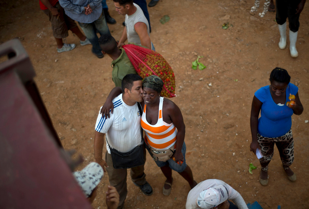 . In this Sept. 30, 2013 photo, a vegetable salesman kisses another vendor at the 114th Street Market on the outskirts of Havana, Cuba. Restaurateurs and street vendors shop here, as well as individual consumers, families and even groups of neighbors who pool their money to buy in bulk. (AP Photo/Ramon Espinosa)
