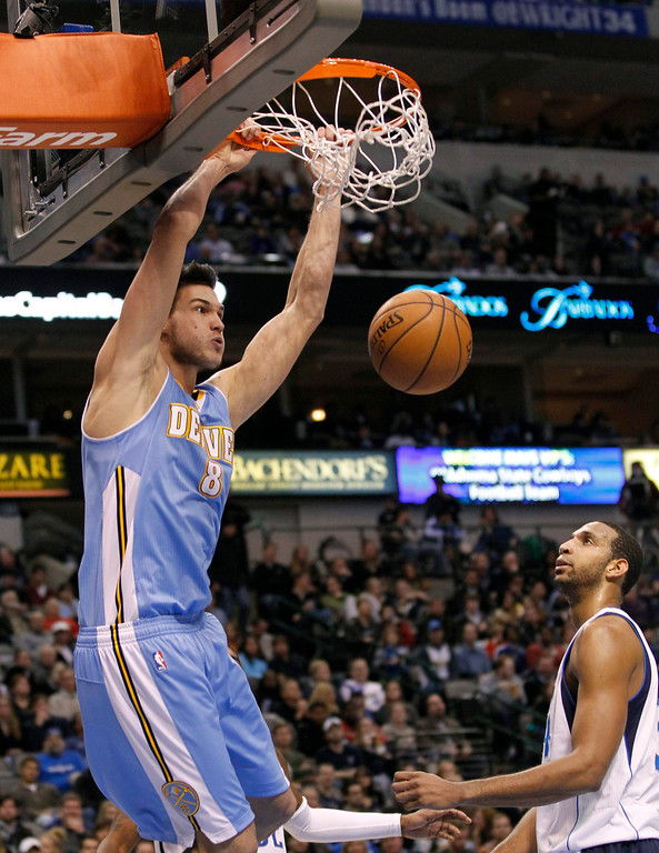 . Denver Nuggets forward Danilo Gallinari dunks the ball as Dallas Mavericks center Brandan Wright watches during the second half of their NBA basketball game in Dallas, Texas December 28, 2012.  REUTERS/Mike Stone (UNITED STATES - Tags: SPORT BASKETBALL)