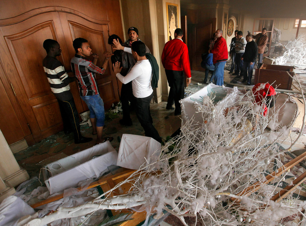 . A Christmas tree and damaged furniture are seen at a wedding hall as policemen try to extinguish fire at a police club set by protesters following a court verdict in Cairo, Egypt, Saturday, March 9, 2013. (AP Photo/Amr Nabil)