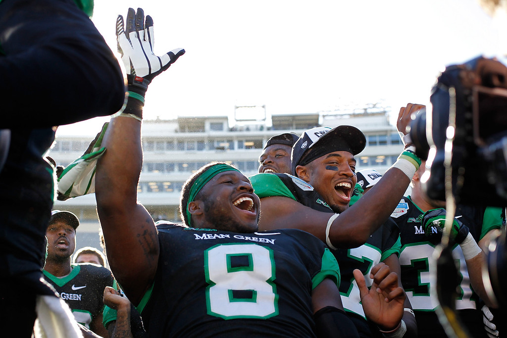 . DALLAS, TX - JANUARY 01: Mark Lewis #8 of the North Texas Mean Green celebrates with his teammates after defeating the UNLV Rebels in the Heart of Dallas Bowl at Cotton Bowl Stadium on January 1, 2014 in Dallas, Texas. The North Texas Mean Green defeated the UNLV Rebels 36-14.  (Photo by Sarah Glenn/Getty Images)