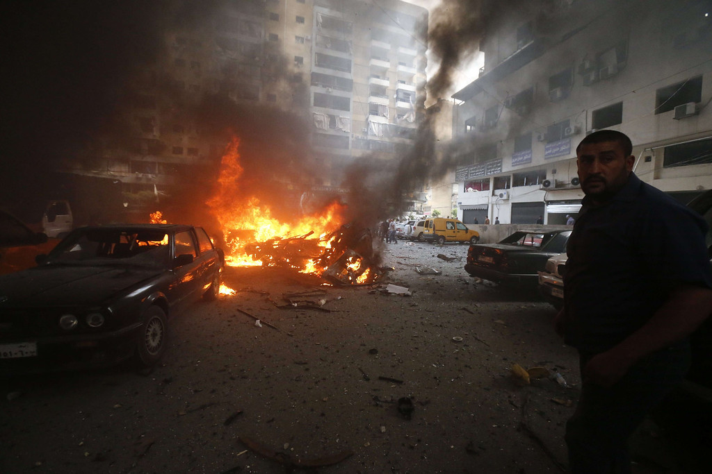 . Residents gather at the site of an explosion in Beirut\'s southern suburb neighborhood of Bir al-Abed on July 9, 2013.   AFP PHOTO/STR-/AFP/Getty Images