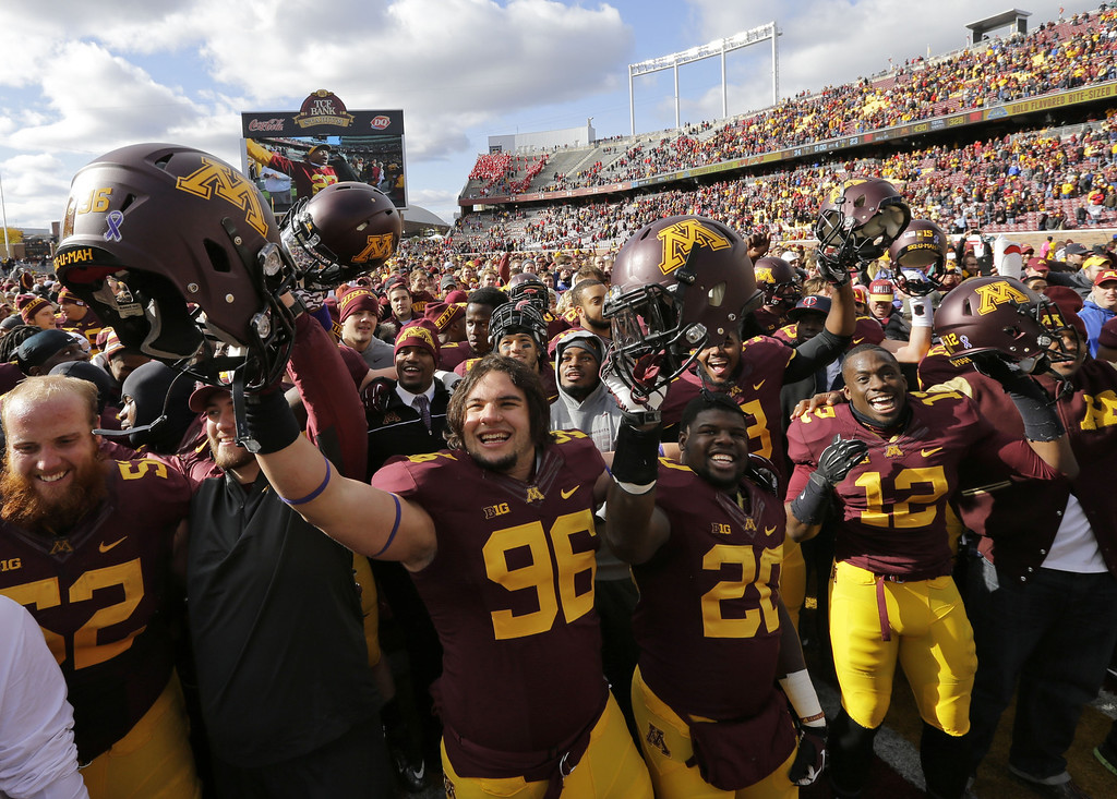 . Minnesota defensive lineman Jordan Hinojosa (96) and teammates and fans celebrate after Minnesota beat No. 25 Nebraska 34-23 in an NCAA college football game in Minneapolis Saturday, Oct. 26, 2013.  (AP Photo/Ann Heisenfelt)