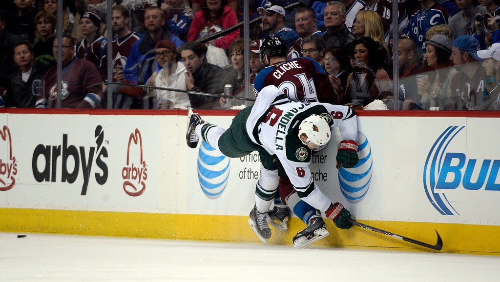. Marc-Andre Cliche (24) of the Colorado Avalanche gets tied up against the boards with Marco Scandella (6) of the Minnesota Wild during the second period of action. The Colorado Avalanche hosted the Minnesota Wild in the first round of the Stanley Cup Playoffs at the Pepsi Center in Denver, Colorado on Saturday, April 19, 2014. (Photo by John Leyba/The Denver Post)