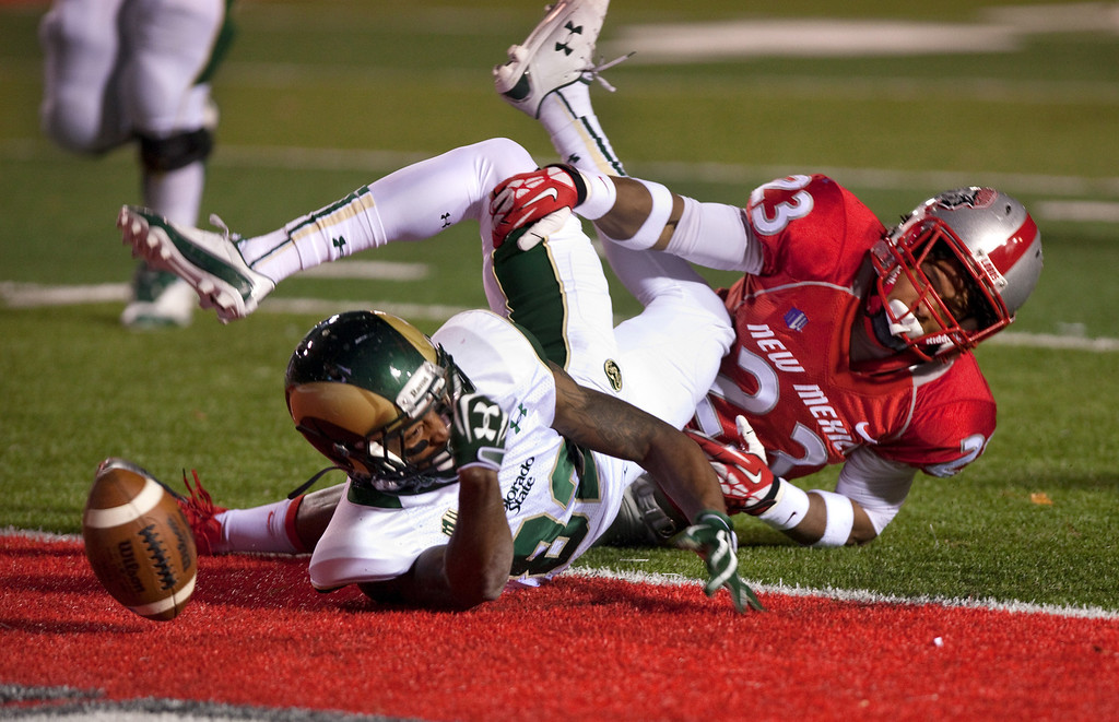 . Colorado State wide receiver Rashard Higgins, left, loses the ball after crossing the goal line for a touchdown against New Mexico\'s Devonta Tabannah in the first half of an NCAA college football game on Saturday, Nov. 16, 2013, in Albuquerque, N.M. (AP Photo/Eric Draper)