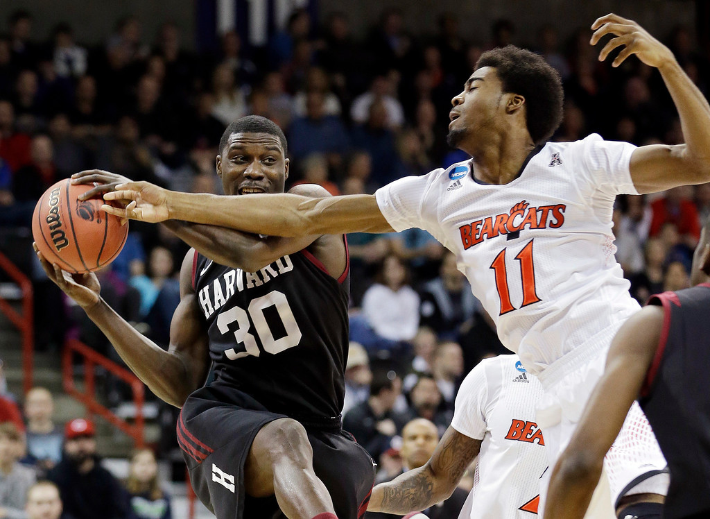 . Harvard\'s Kyle Casey (30) tries to hold onto a rebound in front of Cincinnati\'s Jermaine Lawrence during the first half of a second-round game in the NCAA college basketball tournament in Spokane, Wash., Thursday, March 20, 2014. (AP Photo/Elaine Thompson)