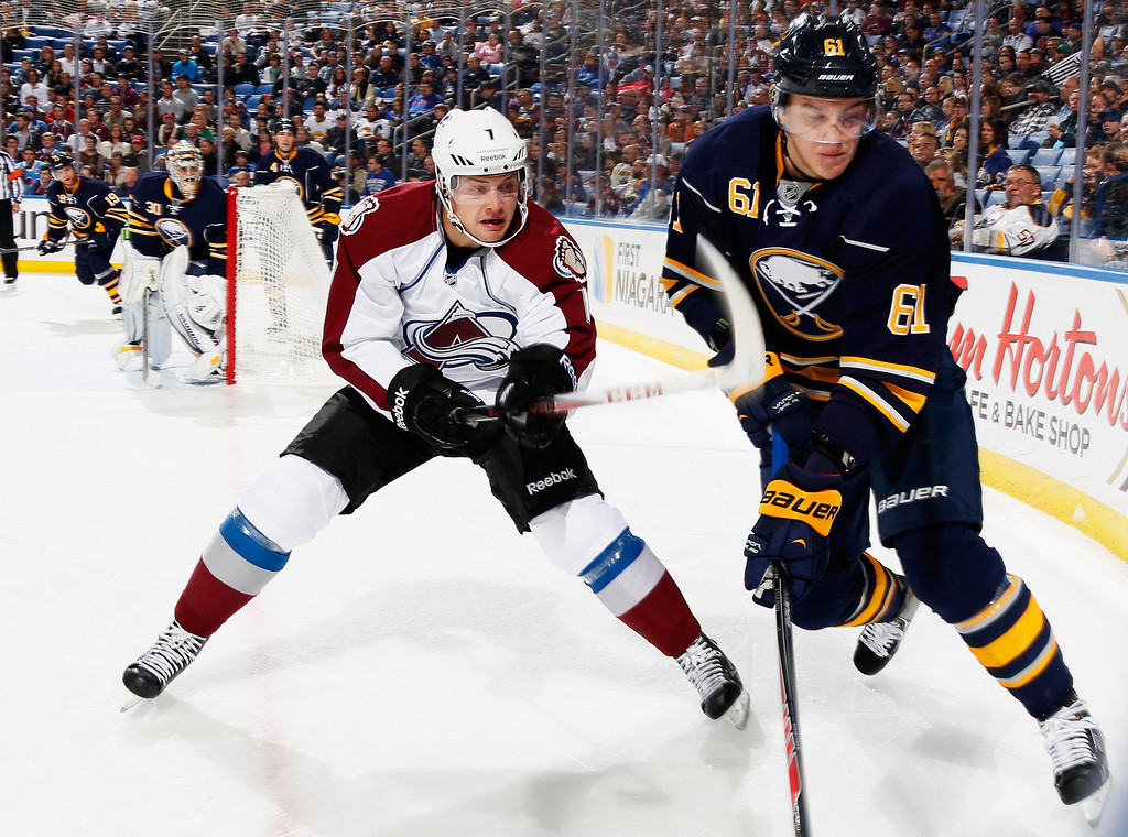 . BUFFALO, NY - OCTOBER 19:  Nikita Zadorov #61 of the Buffalo Sabres in his first NHL hockey game and John Mitchell #7 of the Colorado Avalanche fight for the puck at First Niagara Center on October 19, 2013 in Buffalo, New York.  (Photo by Jen Fuller/Getty Images)