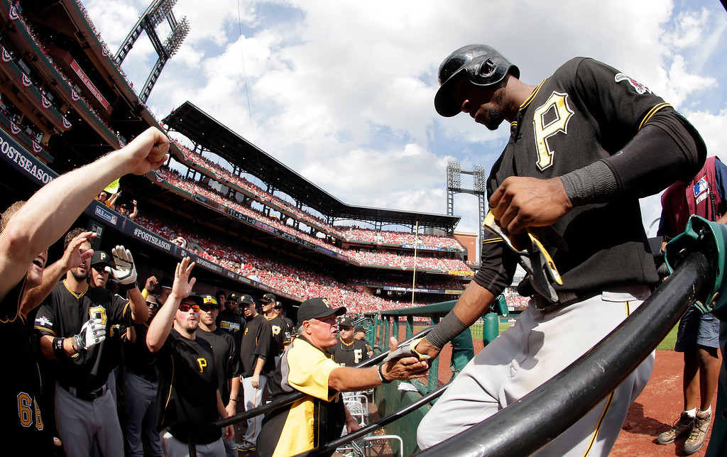 . In this image taken with a fisheye lens, Pittsburgh Pirates\' Starling Marte, right, is congratulated by manager Clint Hurdle, center, as teammates greet him at the dugout after hitting a home run against the St. Louis Cardinals in the eighth inning of Game 2 of baseball\'s National League division series on Friday, Oct. 4, 2013, in St. Louis. The Pirates won 7-1. (AP Photo/Charlie Riedel)