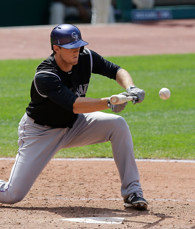 . Colorado Rockies\' DJ LeMahieu bunts against Cleveland Indians relief pitcher Bryan Shaw in the seventh inning of a baseball game on Sunday, June 1, 2014, in Cleveland. LeMahieu was out at first base. (AP Photo/Tony Dejak)