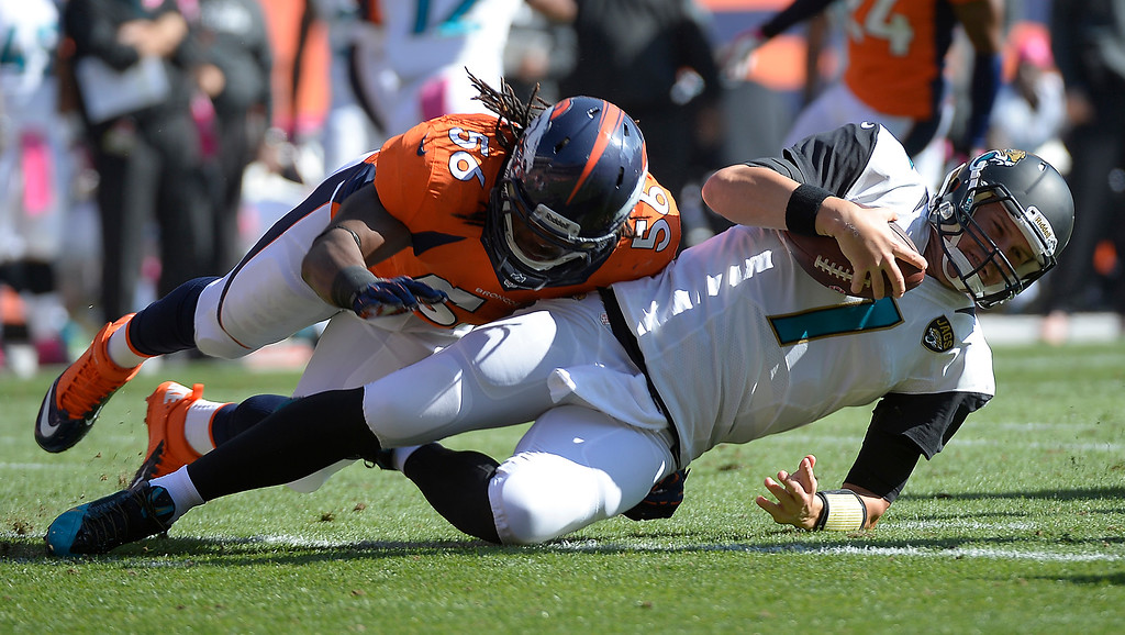 . Jacksonville Jaguars quarterback Chad Henne (7) falls after being hit by Denver Broncos defensive tackle Kevin Vickerson (99) while Denver Broncos outside linebacker Nate Irving (56) finishes the tackle in the first quarter.  (Photo by John Leyba/The Denver Post)