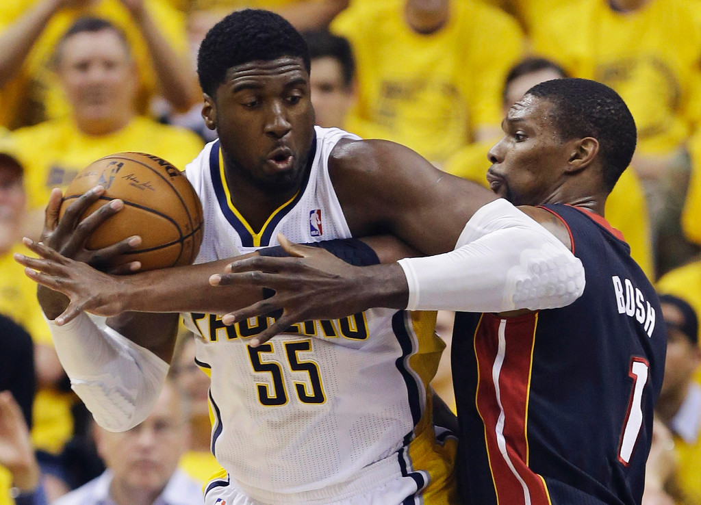. Indiana Pacers center Roy Hibbert (55) is defended by Miami Heat center Chris Bosh (1) during the first half of Game 5 of the NBA basketball Eastern Conference finals, in Indianapolis, Wednesday, May 28, 2014. (AP Photo/Michael Conroy)