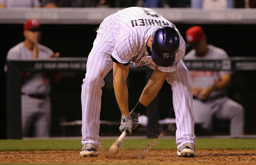 . DENVER, CO - AUGUST 15:  DJ LeMahieu #9 of the Colorado Rockies strikes the ground as he reacts to striking out against Johnny Cueto #47 of the Cincinnati Reds with the bases loaded to end the sixth inning at Coors Field on August 15, 2014 in Denver, Colorado.  (Photo by Doug Pensinger/Getty Images)