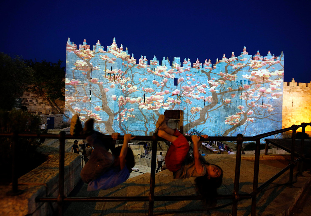 ". Children play in front of Damascus gate outside Jerusalem\'s Old City as it is projected with images during the ""Jerusalem Light 2013\"" Festival June 5, 2013. The festival opened on Wednesday night and will run for a week in the Old City of Jerusalem, hosting Israeli and international artists who will display their installations throughout the week. REUTERS/Ammar Awad"
