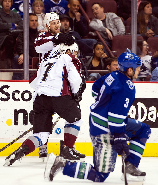 . John Mitchell #7 of the Colorado Avalanche is congratulated by teammate Ryan O\'Reilly #90 after scoring an empty net goal while Kevin Bieksa #3 of the Vancouver Canucks gets up from the ice during the third period in NHL action on April 10, 2014 at Rogers Arena in Vancouver, British Columbia, Canada.  (Photo by Rich Lam/Getty Images)