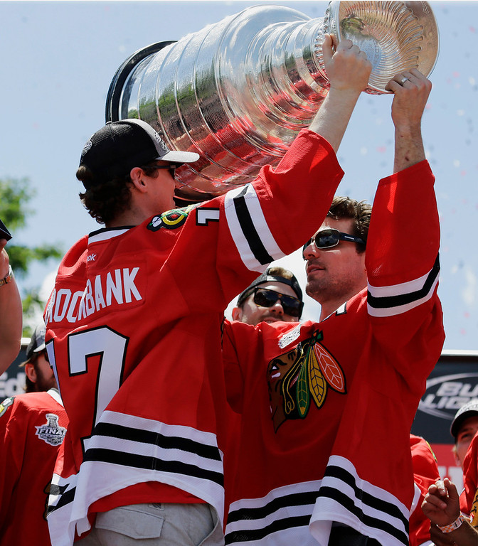 . Chicago Blackhawks\' Patrick Sharp, right, passes off the Stanley Cup to teammate Sheldon Brookbank during a rally for the Stanley Cup hockey champions in Grant Park Friday, June 28, 2013, in Chicago. (AP Photo/Nam Y. Huh)