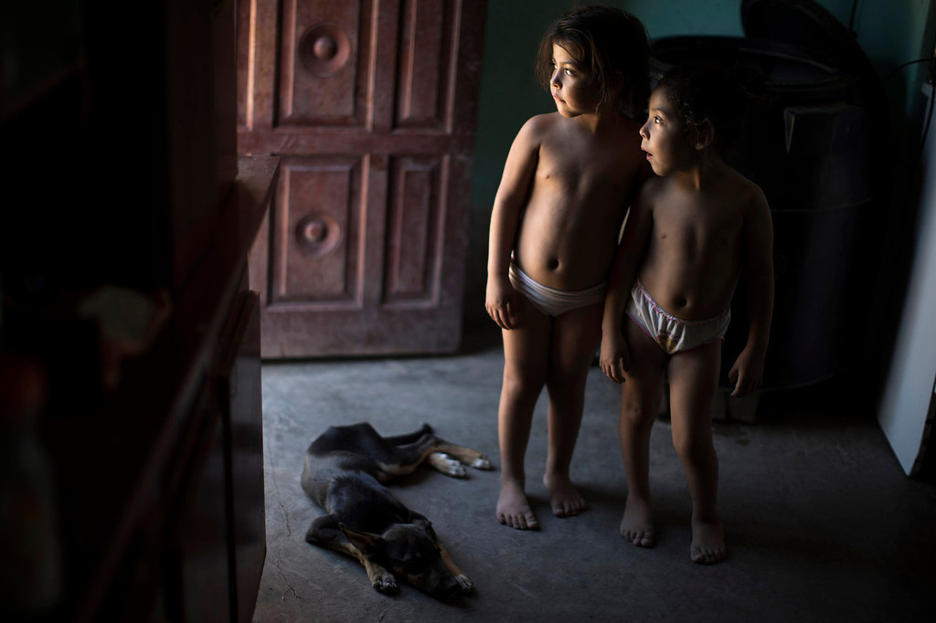 . Erika, right, and her twin sister Macarena, who suffer from chronic respiratory illness, stand inside their home in Avia Terai, in Chaco province, Argentina on March 31, 2013. The twins\' mother, Claudia Sariski, whose home has no running water, says she doesn\'t let her children drink from the discarded pesticide containers she keeps in her dusty backyard. But her chickens do, and she has no other water to wash the family\'s clothes with. (AP Photo/Natacha Pisarenko)