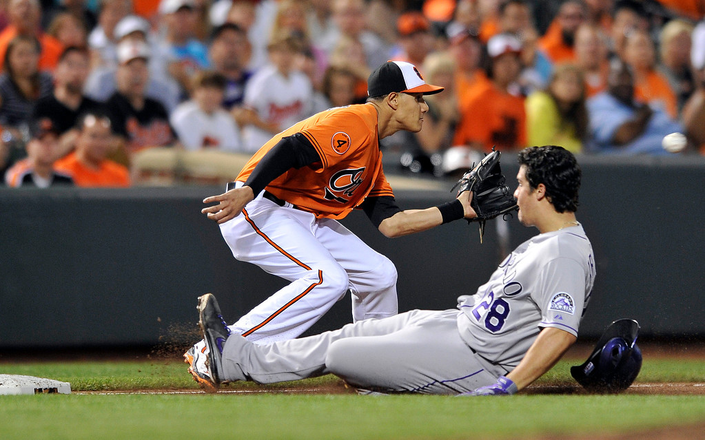 . Colorado Rockies\' Nolan Arenado (28) slides into third base as Baltimore Orioles third baseman Manny Machado covers in the sixth inning of a baseball game on Saturday, Aug. 17, 2013, in Baltimore. Arenado was safe and earned a triple. (AP Photo/Gail Burton)