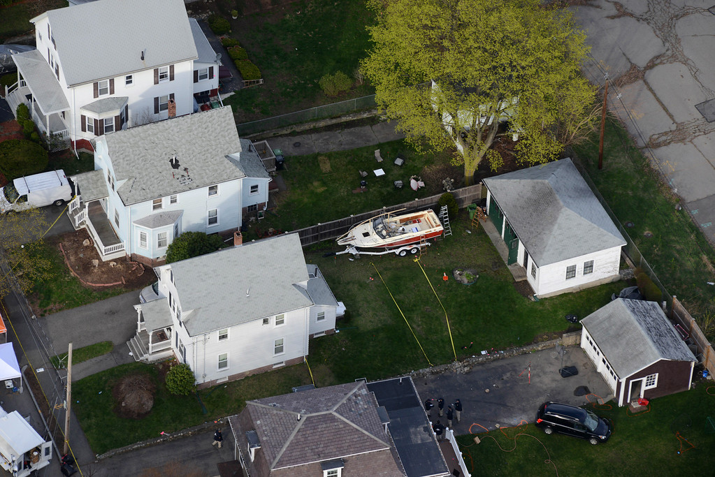 . WATERTOWN, MA - APRIL 20: Investigators work around the boat where Dzhokhar A. Tsarnaev was found hiding after a massive manhunt, in the backyard of a Franklin Street home, in an aerial view April 20, 2013 in Watertown, Massachusetts. A manhunt for Dzhokhar A. Tsarnaev, 19, a suspect in the Boston Marathon bombing ended after he was apprehended on a boat parked on a residential property in Watertown, Massachusetts. His brother Tamerlan Tsarnaev, 26, the other suspect, was shot and killed after a car chase and shootout with police. The bombing, on April 15 at the finish line of the marathon, killed three people and wounded at least 170. (Photo by Darren McCollester/Getty Images)