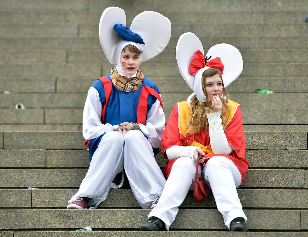 ". Two girls waiting on stairs in a street when tens of thousands of revelers dressed in carnival costumes celebrate the start of the street-carnival on the so called ""Old Women\'s Day\"" in the party capital Cologne, Germany, Thursday, Feb. 27, 2014. (AP Photo/Martin Meissner)"